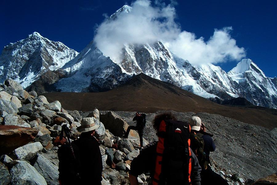 Trekkers enjoying the view of towered peak Pumori